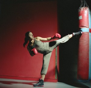 Young female boxer kicking punch bag